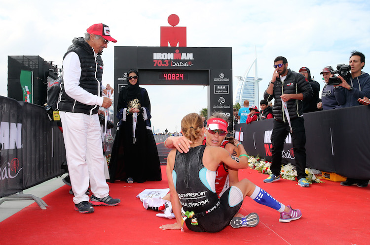 DUBAI, UNITED ARAB EMIRATES - JANUARY 29:  Caroline Steffen of Switrzerland (red) and Kaisa Lehtonen of Finland who finished second and third respectivly hug each other as they lay collapsed after finishing the Women's IRONMAN 70.3 Dubai on January 29, 2016 in Dubai, United Arab Emirates.  (Photo by Warren Little/Getty Images for Ironman)